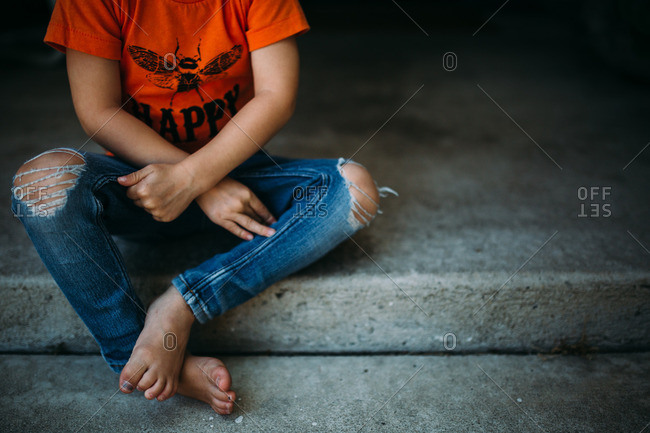 Child sits on front porch