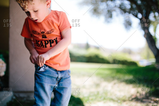 Child tries to reach hand into pocket