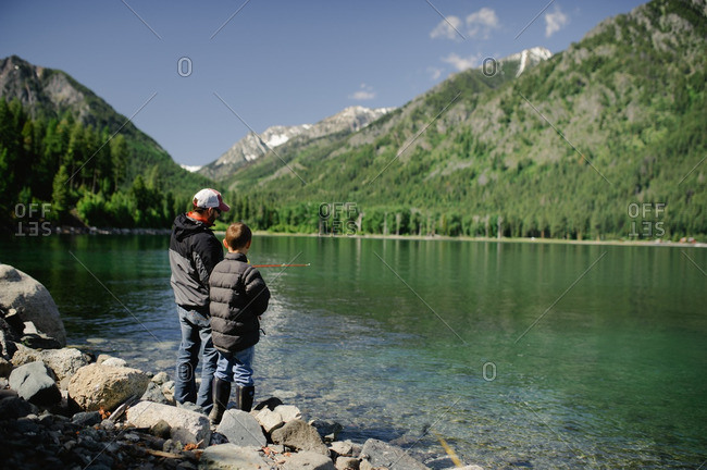 Man and boy fishing on lake