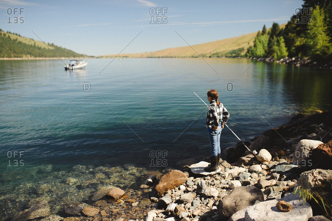 Boy with fishing pole on lakeshore