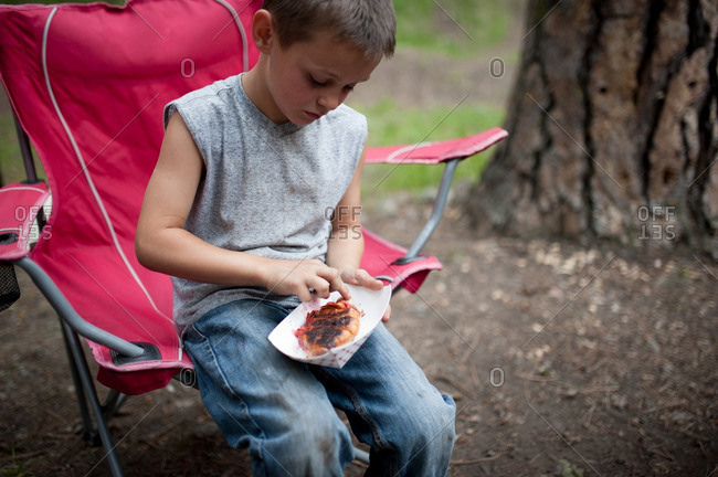 Boy in camping chair with food