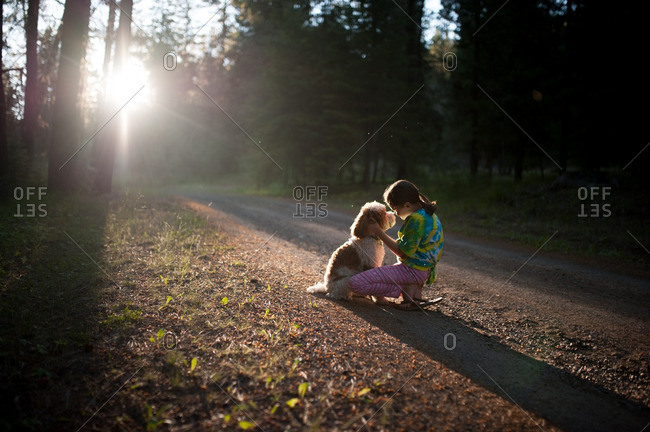 Girl and dog on sunlit path