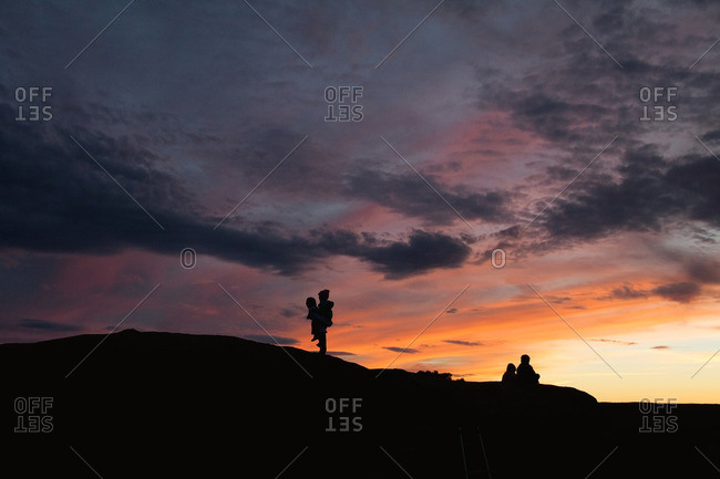 Kids on a hilltop in silhouette