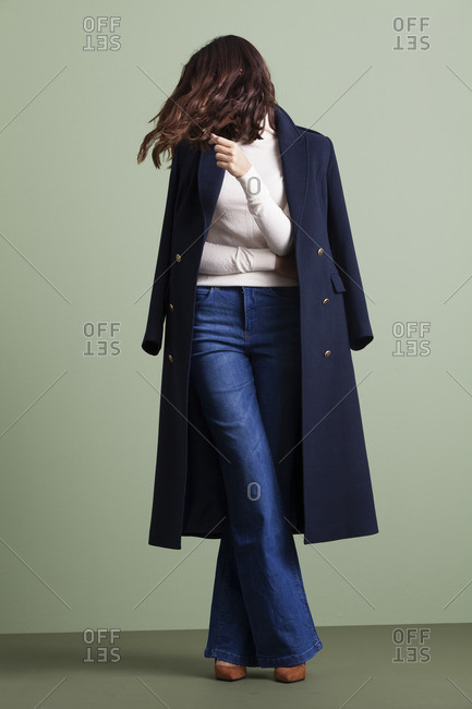 Woman in a navy overcoat and flared jeans