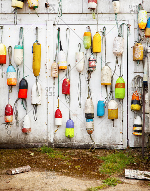 Buoys hanging on the side of an old shed
