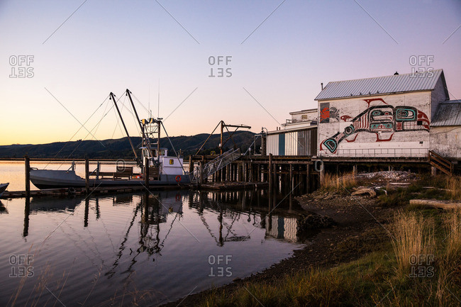 Fishing boat anchored alongside a cannery at dusk