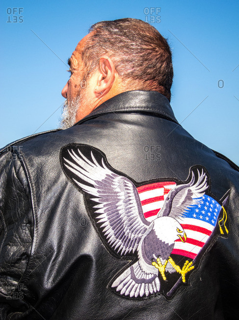 Man wearing a leather jacket with an eagle and American flag patch