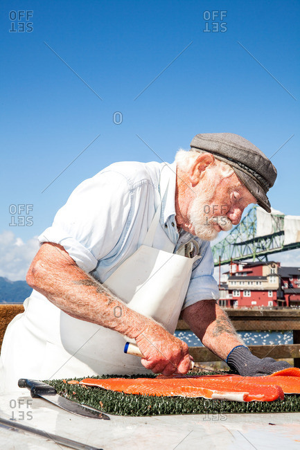 Portrait of a fishmonger cleaning and preparing a fish outdoors