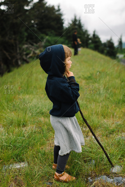 Young girl with walking stick gazing into distance