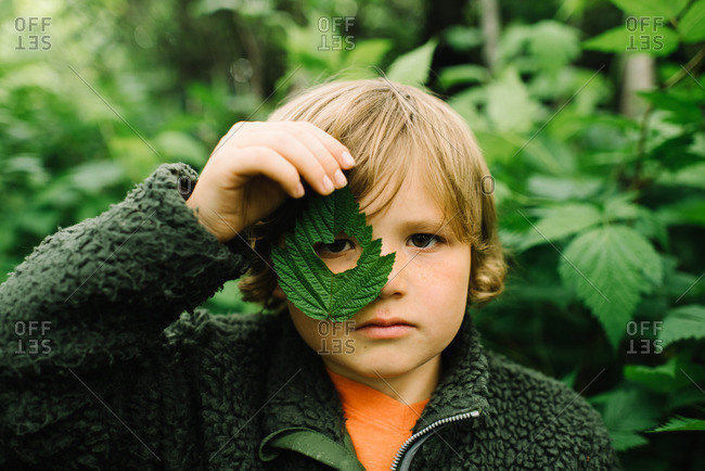 Boy holding  leaf with hole over his eye