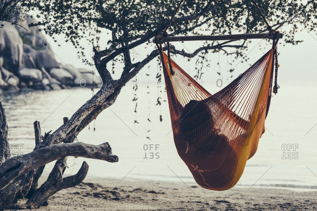 Woman in hanging beach hammock