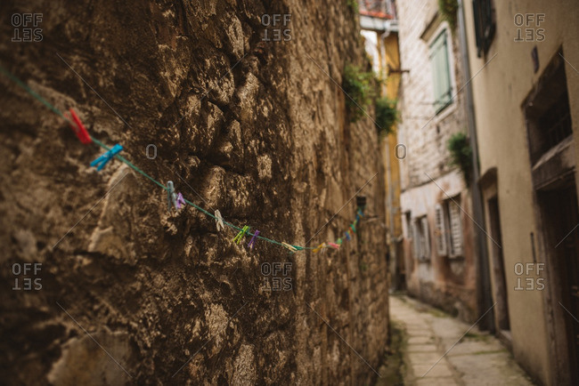 Colorful clothespins on line against stone wall in alleyway