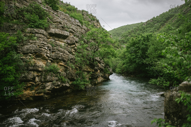 Scenic view of river rushing past rocky cliffs