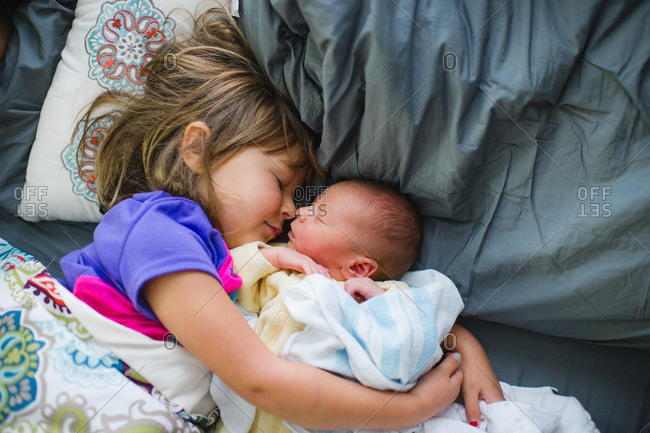 Big sister holding her baby brother in bed