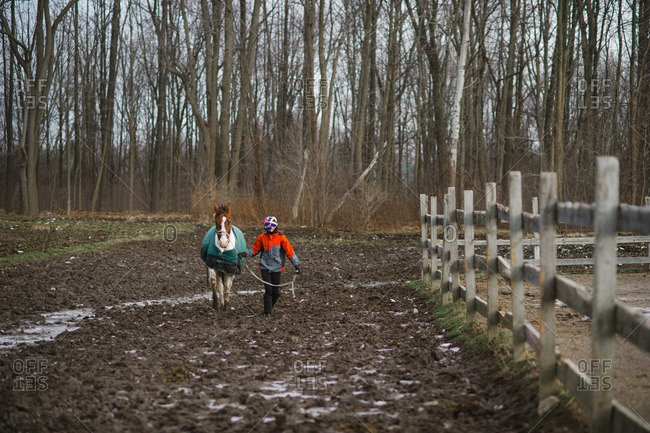 Girl walking a horse through a muddy paddock