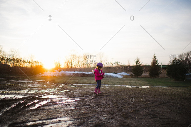 Girl walking through a muddy paddock on a farm