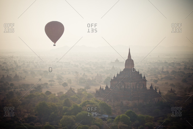 Hot air balloon floating over temple in Bagan, Myanmar