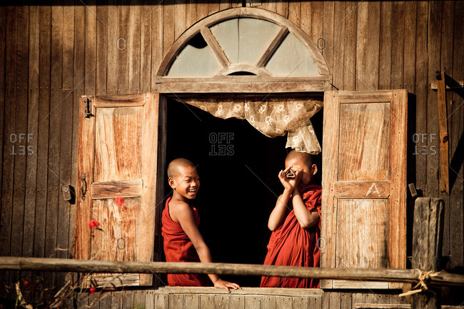 Two monks standing in front of window at Wai Gyi Monastery, Kalaw, Myanmar