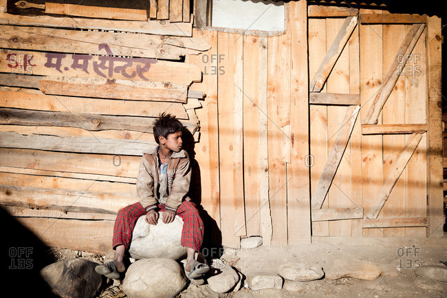 Boy sitting on rock in Jumla, Nepal