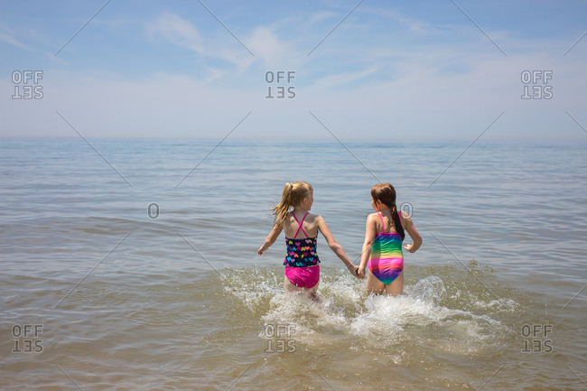 Two girls wading and holding hands