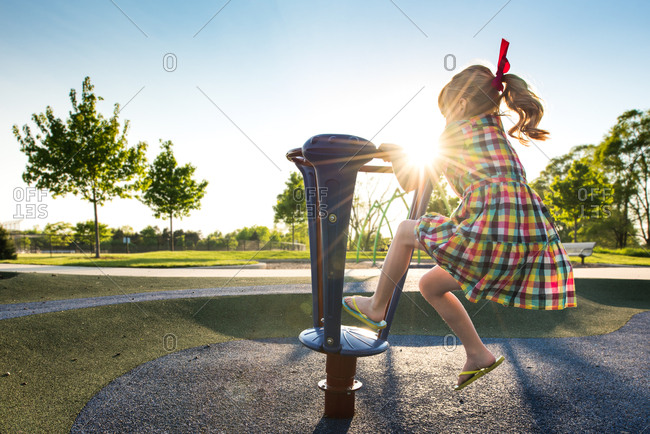 Girl spinning on playground equipment