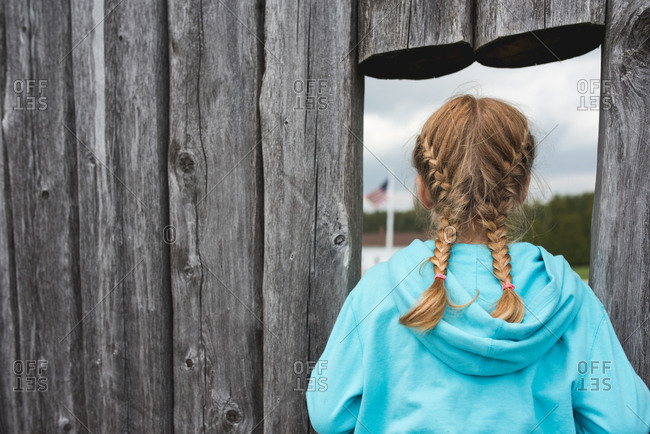 Girl looking through hole in fence