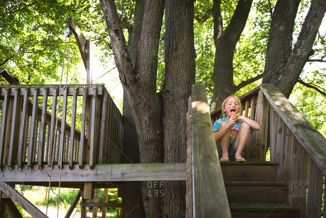 Girl eating popsicle in tree fort