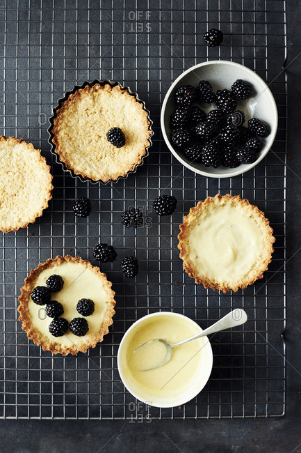 Fresh blackberry and vanilla custard tarts on a wire baking rack