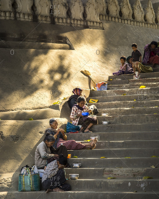 Myanmar - June 30, 2016: Women begging for money and food on the steps of the pier in Myanmar