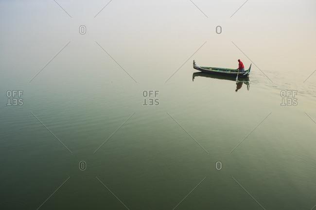 A lone boatman paddles his boat across a placid lake