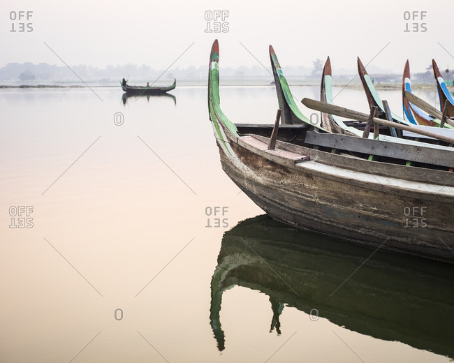 Fishing boats lined up at sunrise near the U Bein Bridge in Mandalay, Myanmar