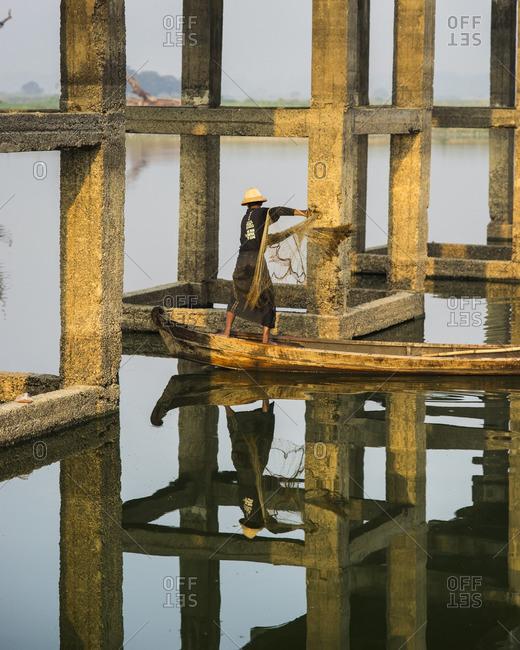 A fisherman throws his net under the U Bein Bridge in Mandalay, Myanmar