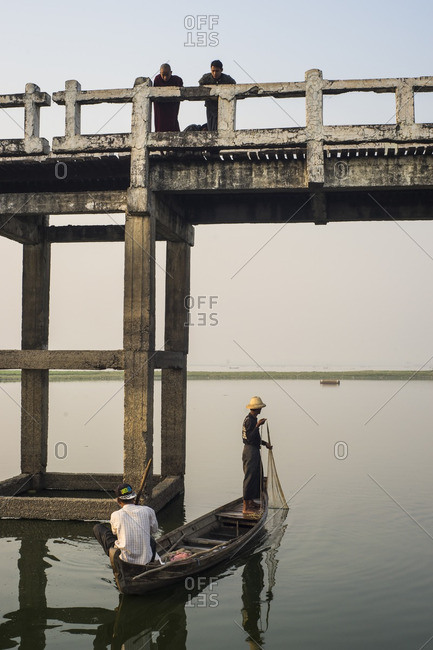 Myanmar - June 30, 2016: Two fishermen being watched by novice monks