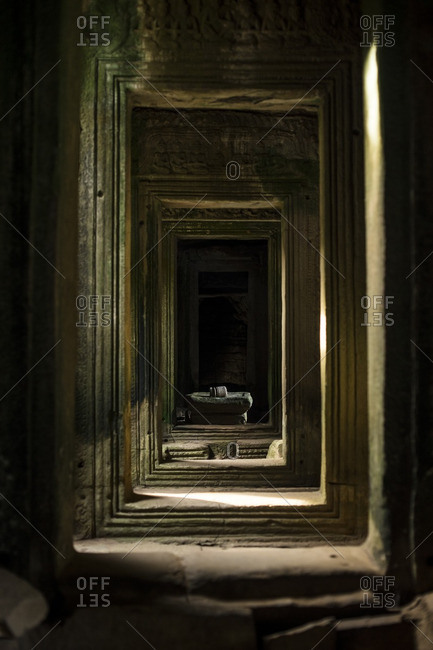 Light highlighting a broken Yoni pedestal in an ancient temple hallway in Angkor Wat