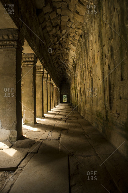 Sunlight streaming between columns in an ancient temple hallway in Angkor Wat