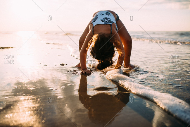 Girl bent over playing on a beach shore