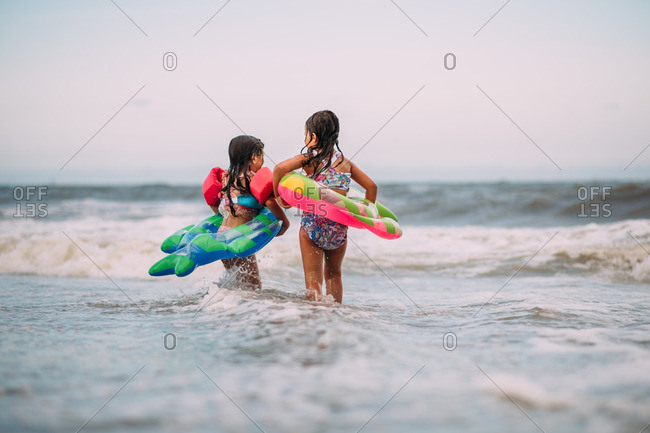 Little girls playing in the ocean with floaties