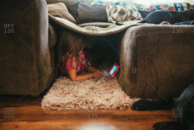 Girl playing with tablet in living room fort