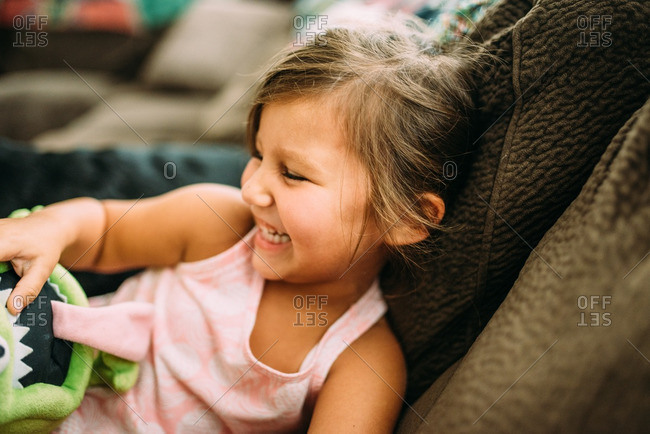 Girl sitting on a living room sofa holding stuffed toy