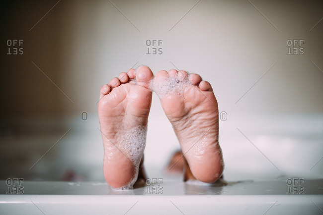 Child's soapy feet on edge of bathtub