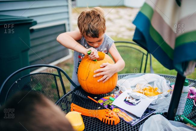 Little boy carving a pumpkin on a patio table
