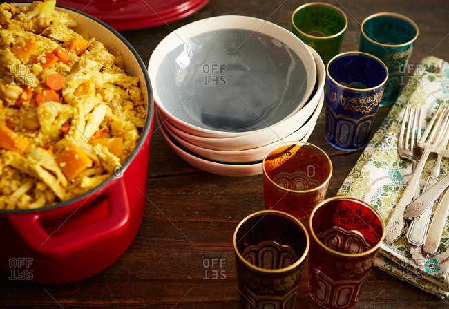 One-pot couscous dish with bowls and colorful Moroccan glasses