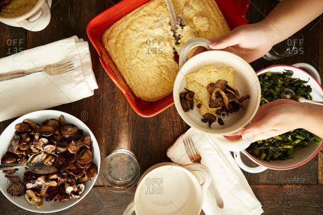 Hands holding bowl of polenta with sauteed wild mushrooms