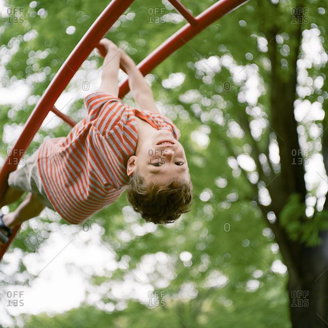 Boy dangling upside down on monkey bars