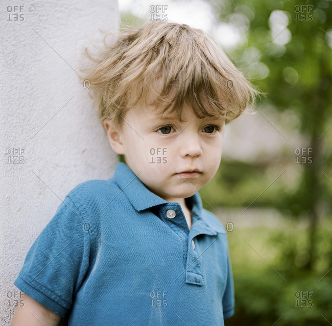 Portrait of a toddler boy leaning against wall