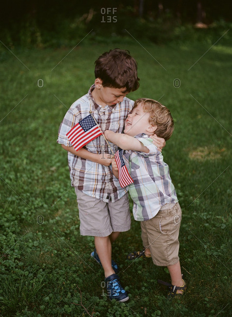 Two young brothers with American flags hug each other