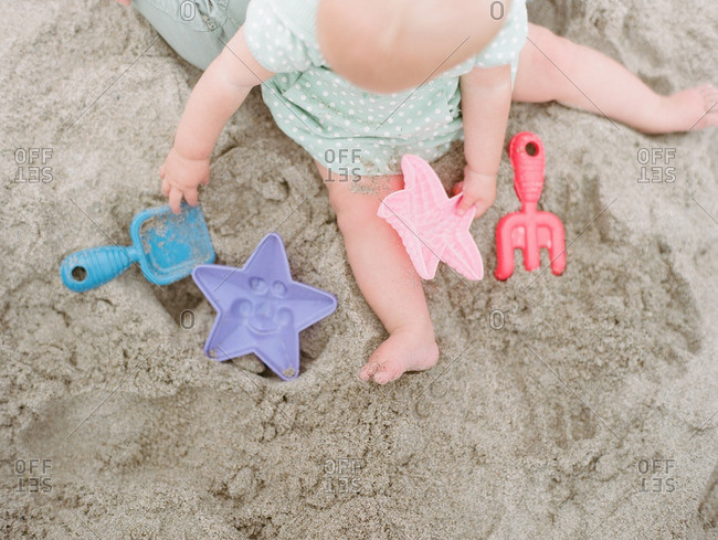 Toddler on beach with toys