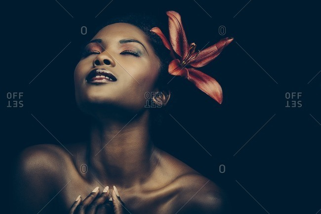 Beautiful woman with red lily in her hair