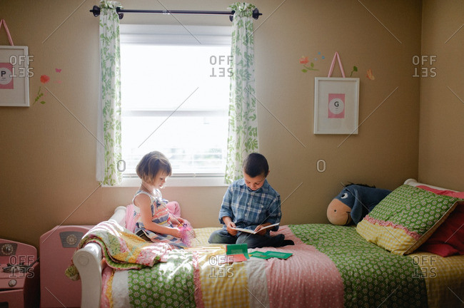Boy and girl playing together on bed