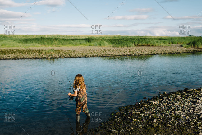 Girl wearing waders fishing in a river